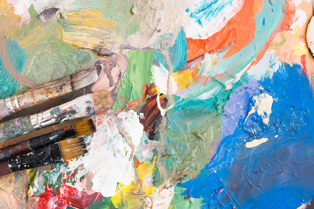 Elevated view of paint brushes over colorful messy background