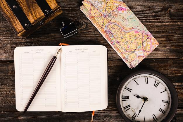 Vista elevata di penna, diario, mappa e orologio su fondo in legno