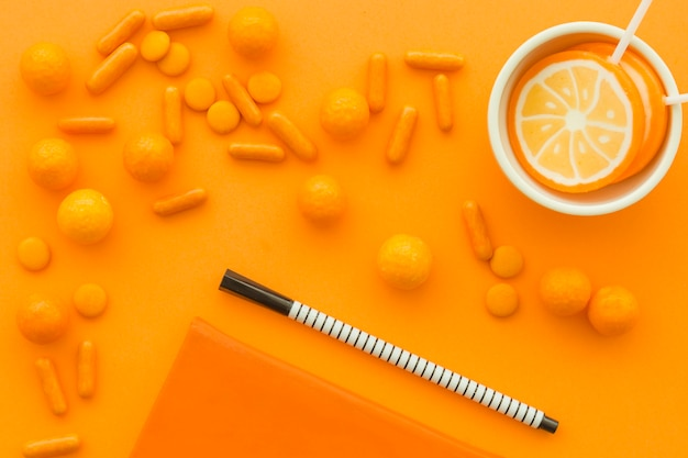 Elevated view of pen and lollipops with scattered candies on orange surface