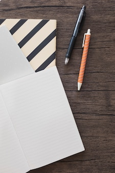 Elevated view of pen; notebook on wooden desk