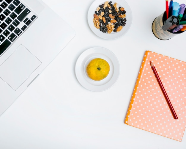 Elevated view of pencil; citrus fruit; notebook; nut food and laptop on white backdrop