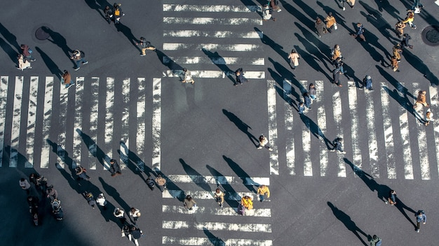 Elevated view over a people on pedestrian crossing in road intersection of japan. aerial view of pedestrians at crosswalk. asia downtown. metropolitan tokyo city
