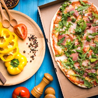 Elevated view of pepperoni pizza in cardboard box with spices; peppermill and vegetables over blue wooden table
