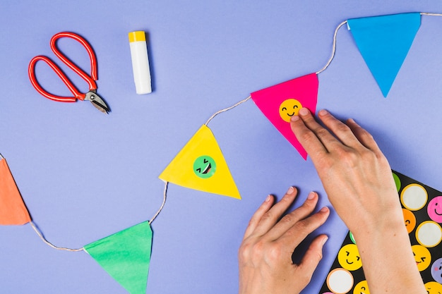 Elevated view of person hand sticking emoji sticker on bunting