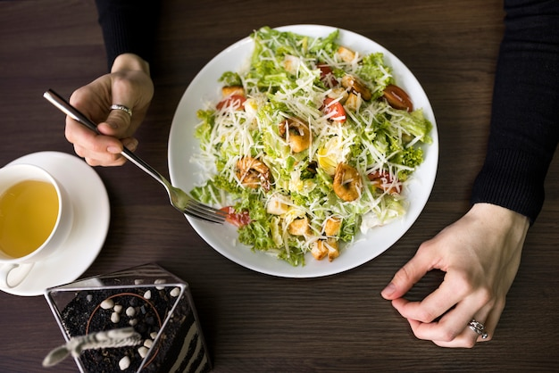 Elevated view of a person having caesar salad with shrimp on white plate over table