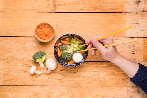 An elevated view of a person's eating vegetables with chopsticks on wooden plank
