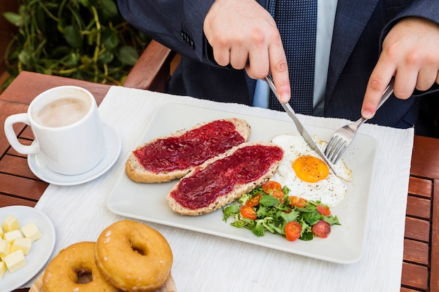 Elevated view of a person's hand eating healthy breakfast