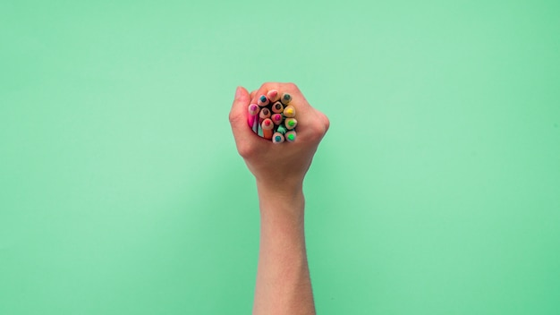 Elevated view of a person's hand holding group of colorful pencils on green background