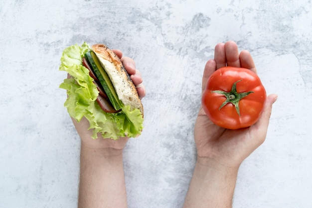 Elevated view of person's hand holding tomato and burger in hand over concrete background