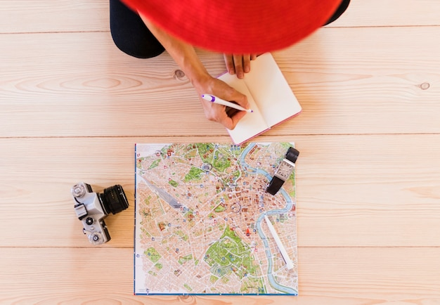 Elevated view of person writing in diary with map; wrist watch and camera on wooden table