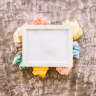Elevated view of picture frame over multi colored crumpled paper