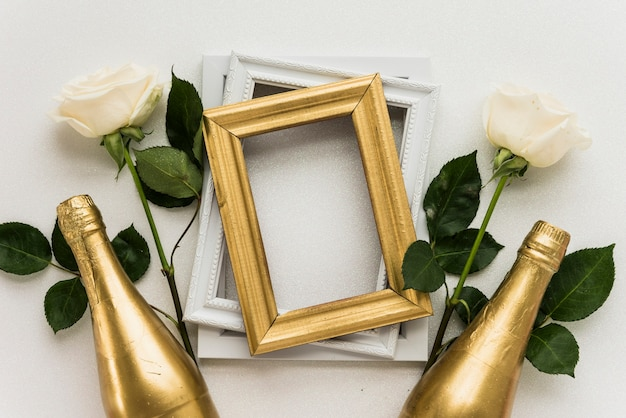 Elevated view of picture frames with two roses and champagne bottle on white surface