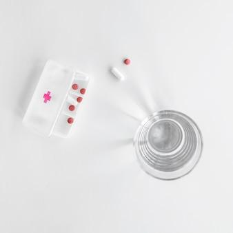 Vista elevata della scatola di pillole vicino a bicchiere d'acqua