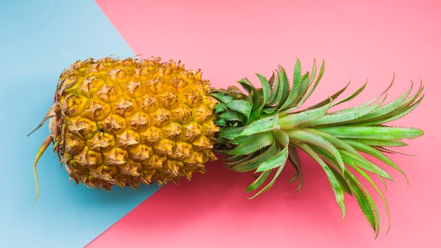 Elevated view of pineapple and blue cardboard paper on pink background