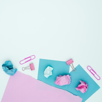 Elevated view of pink and blue card paper and paperclip over white surface