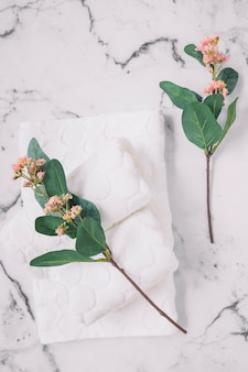 Elevated view of pink flowers and white napkins on marble surface