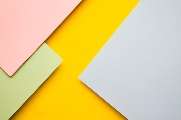 Vista elevata del rosa; carte di cartone verde e grigio su sfondo giallo