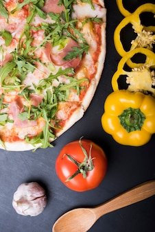 Elevated view of pizza with bacon and arugula leaves near sliced yellow bell pepper; garlic bulb; tomato and wooden spoon