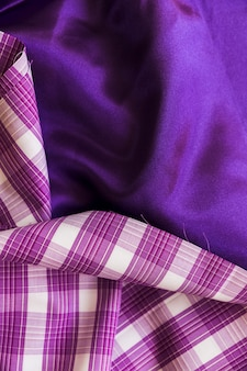 Elevated view of plaid textile on plain purple fabric material