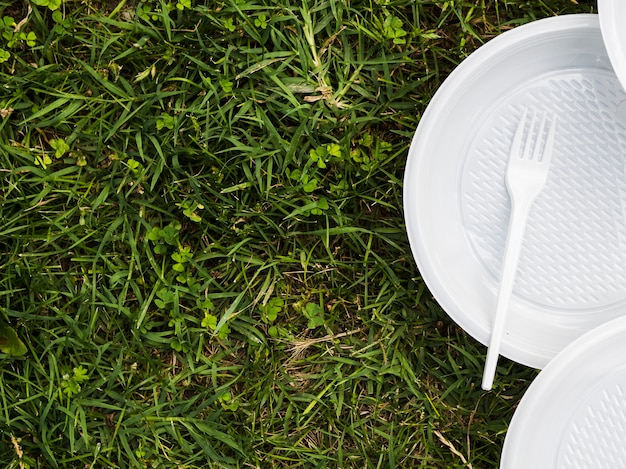 Elevated view of plastic plate and fork on grass at park