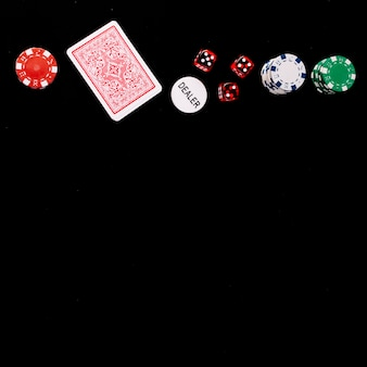 Elevated view of playing cards; dice; poker and dealer chips on black surface