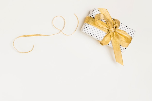 Elevated view of present box wrapped in polka dot design paper with shiny golden ribbon isolated on white backdrop