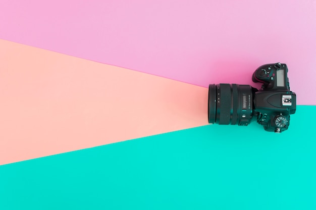 Elevated view of professional camera on colored background