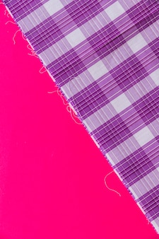 Elevated view of purple chequered pattern textile on pink background