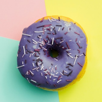 An elevated view of purple donut with sprinkles on colored background