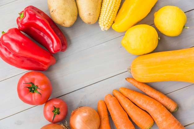 Elevated view of raw vegetables forming frame on wooden background