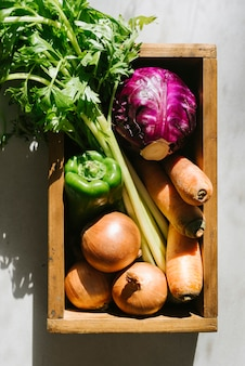 Elevated view of raw vegetables in wooden tray