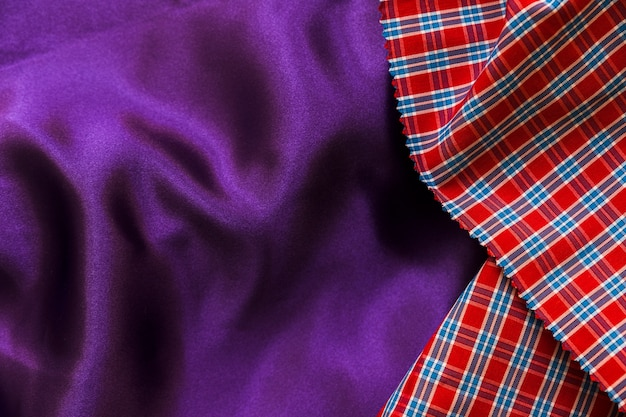 Elevated view of red chequered pattern and plain purple textile