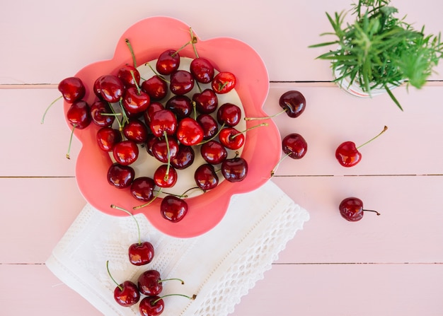 Elevated view of red cherries on flower shaped plate