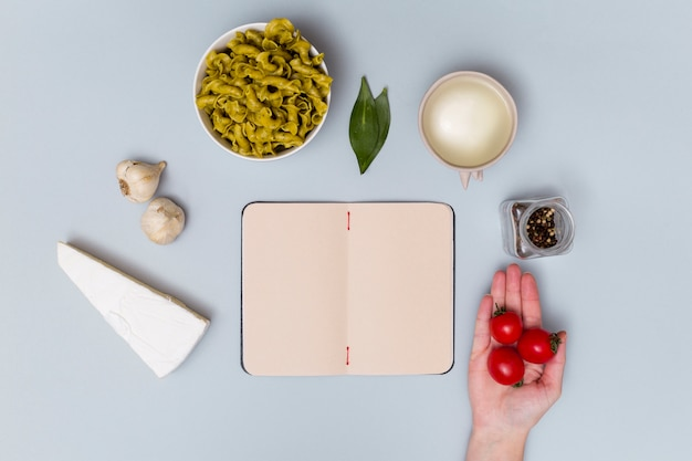 Elevated view of red cherry tomato with pasta ingredient and open notebook