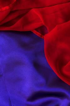 Vista elevata della tessile chiffon rosso su un semplice panno blu
