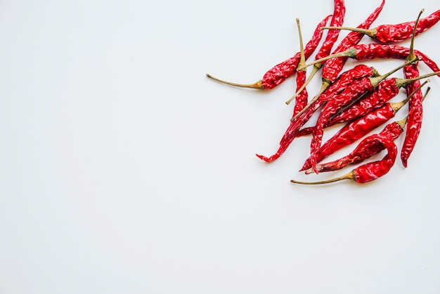 Elevated view of red chilies on white background