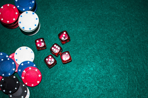 Elevated view of red dices and casino chips on green poker table