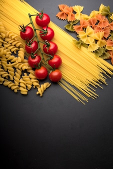 Elevated view of red fresh cherry tomatoes with raw pasta