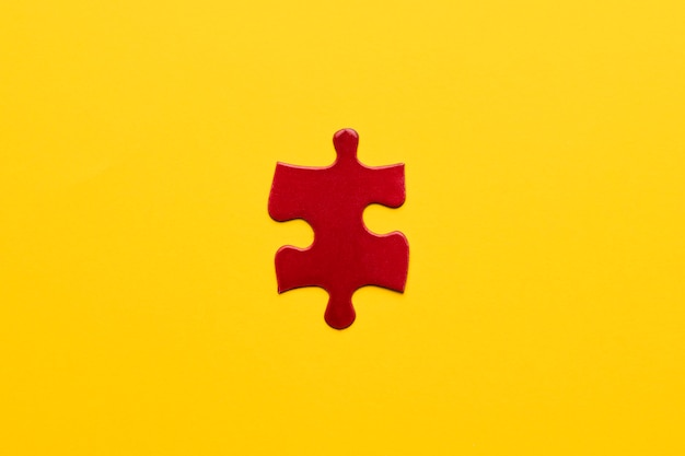 Elevated view of red jigsaw puzzle piece on yellow backdrop