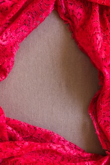 Elevated view of red lace textile on plain sack cloth