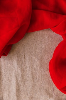 Elevated view of red textile on brown fabric background