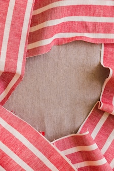Elevated view of red and white stripes fabric material on plain sack cloth