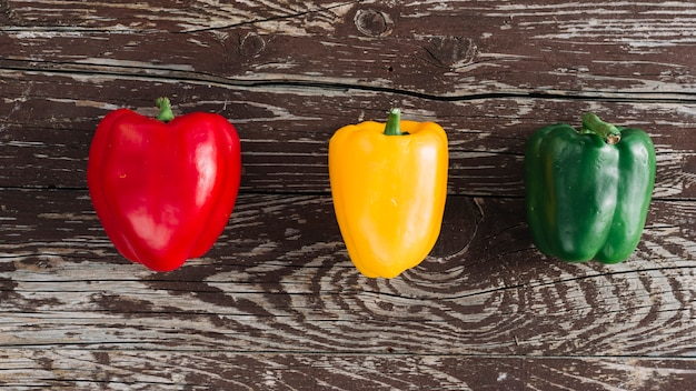 An elevated view of red; yellow and green bell peppers on damaged wooden surface