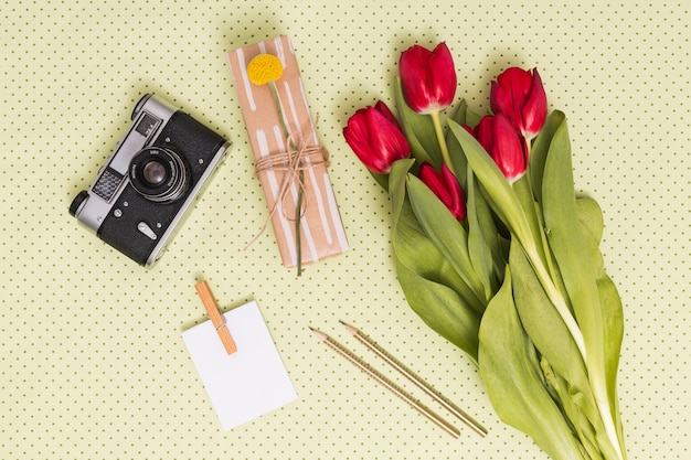 Elevated view of retro camera; blank paper; pencils; gift box and bouquet of tulip flowers over yellow background