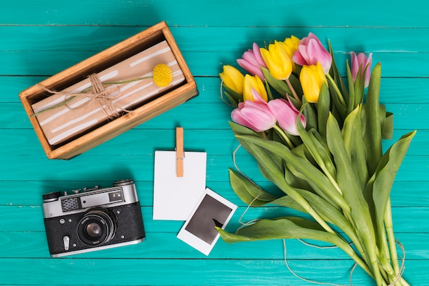 Elevated view of retro camera; gift box; photo copy; and tulip flowers over green wooden backdrop