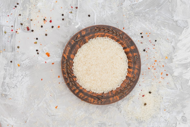 An elevated view of rice grains on plate surrounded with red and black peppercorns on concrete backdrop