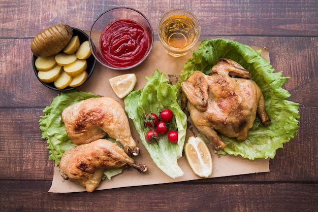 Elevated view of roasted chicken for dinner with beer; potato slices; lemon and sauce on brown paper