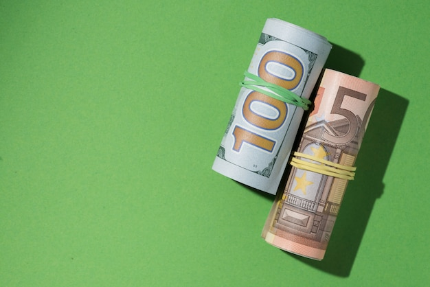 Elevated view of rolled up banknotes on green background