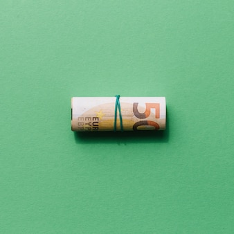 Elevated view of rolled up fifty euro note on green background