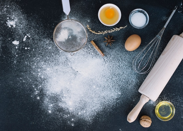 Elevated view of rolling pin; whisk; sieve; egg; walnut; oil and spice on kitchen counter